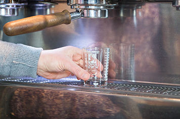 placing an espresso cup beneath an espresso machine