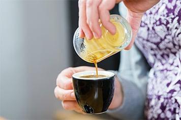 pouring espresso into a mug
