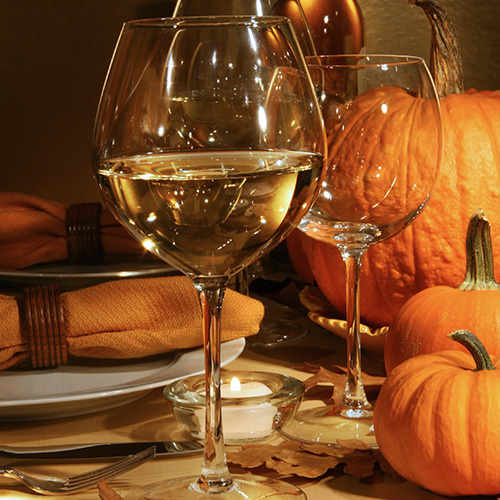 glass of white wine next to empty glasses and pumpkins