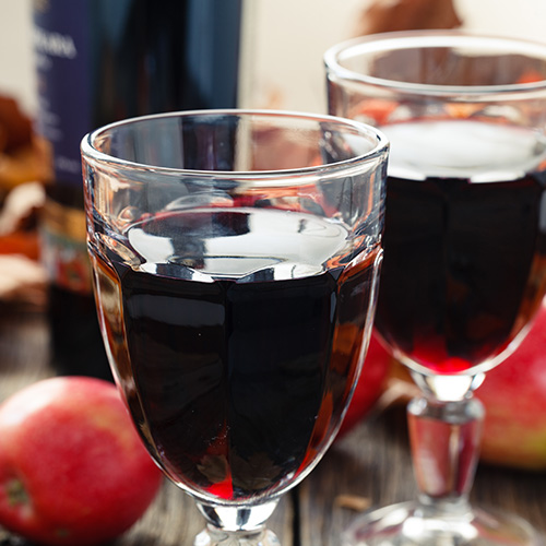 two glasses of red wine with wine bottle and apples behind