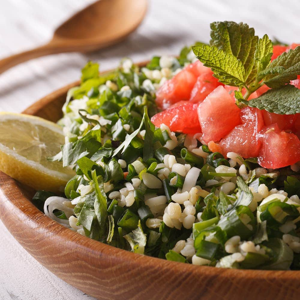 Bowl of tabbouleh with a lemon and mint garnish