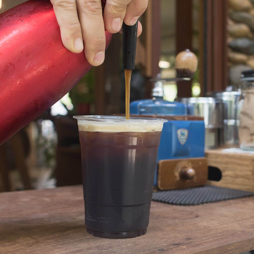 pouring nitro coffee into a plastic cup
