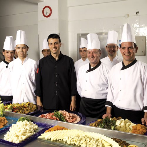 restaurant chefs smiling behind platters of food on table and ready for restaurant opening