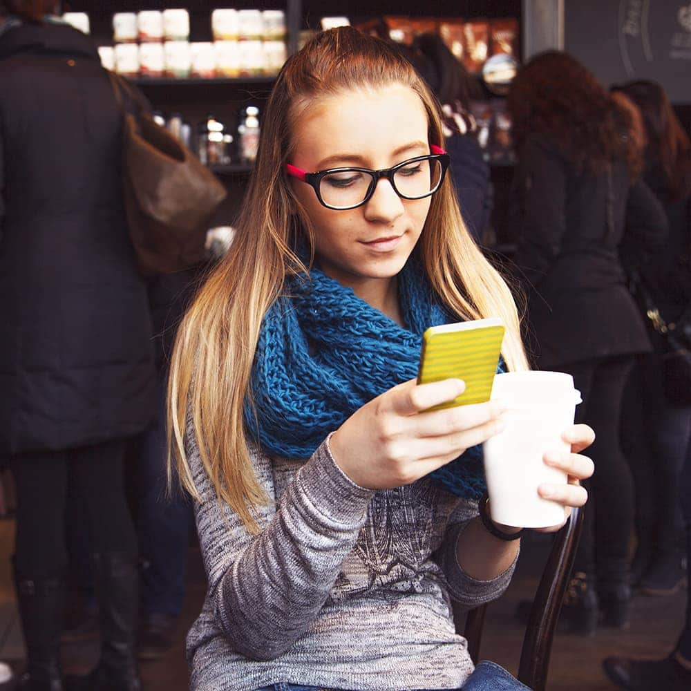 woman wearing a scarf checking her phone and holding a coffee