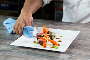 wiping a plate with a microfiber cloth