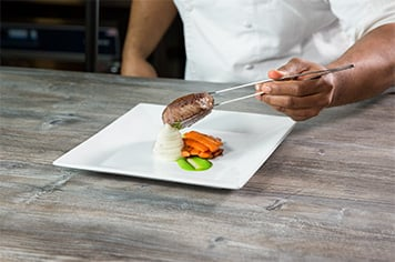 plating a steak using precision tongs
