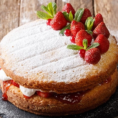 victoria sponge sandwich cake with strawberries and whipped cream