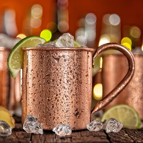 Moscow mule cocktail in a copper mug with ice and limes