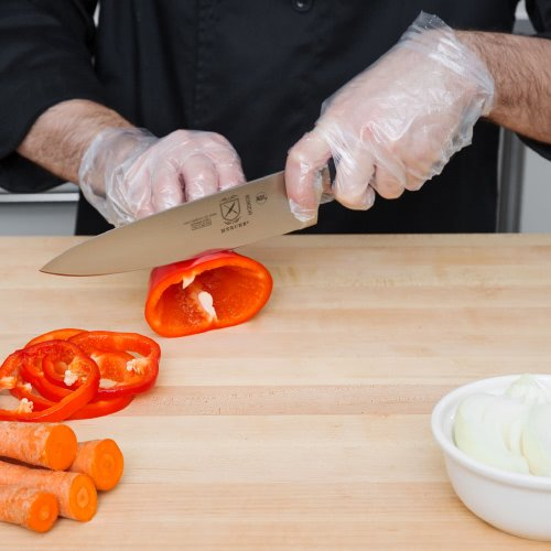 Chef wearing disposable gloves cutting vegetables