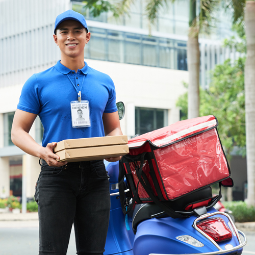 delivery man holding pizzas next to a scooter