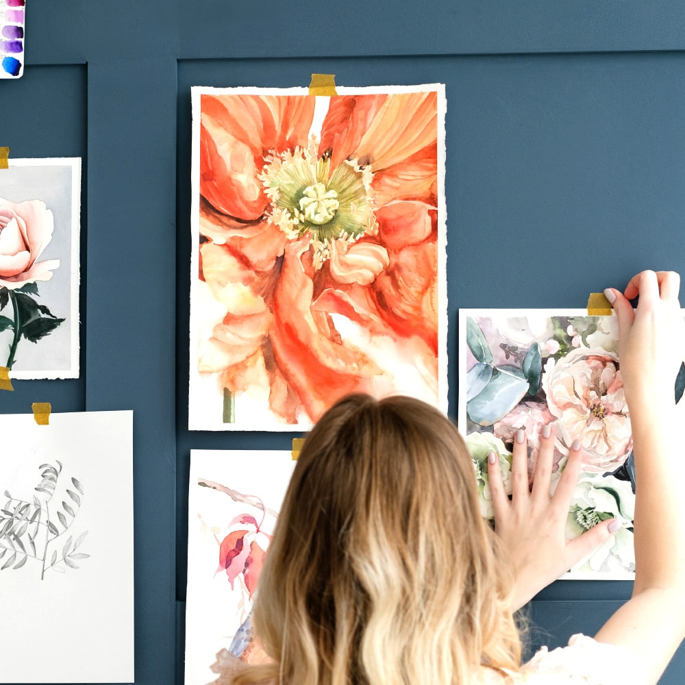 woman hanging painting of flowers on a wall