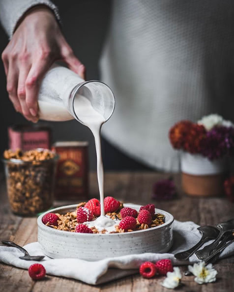 Hand pouring milk over granola with raspberries