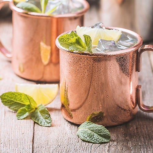 2 unlined copper mugs holding moscow mules surrounded by mint leaves