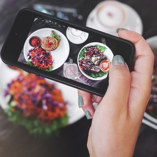 closeup of an iphone taking pictures of a colorful plate of food
