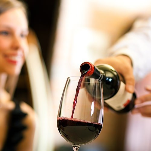 Server's hands pouring wine in front of female guest