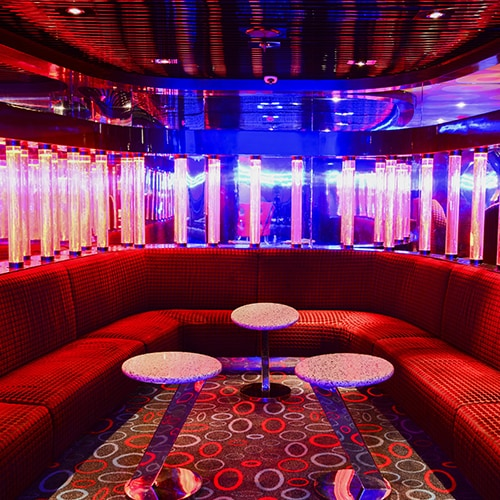 Night club seating with red velvet upholstery and mood lighting