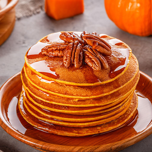 stack of pancakes with maple syrup and pecans on top