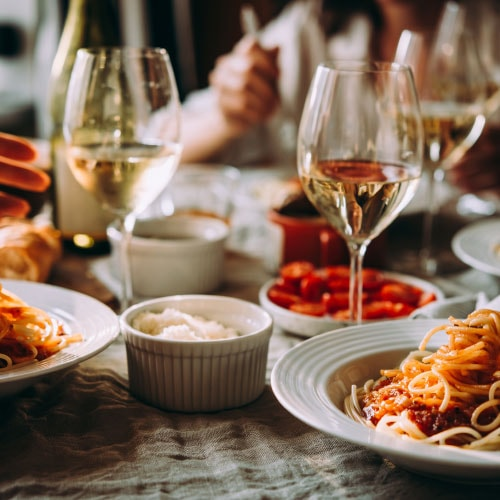 two glasses of white wine next to plates of pasta