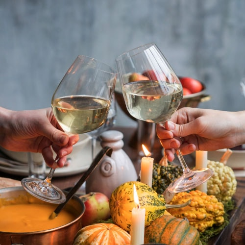 two hands clinking glasses of white wine over Thanksgiving dinner