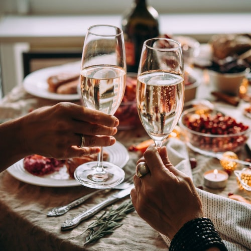 two hands holdings glass of sparkling wine in front of Thanksgiving dinner table
