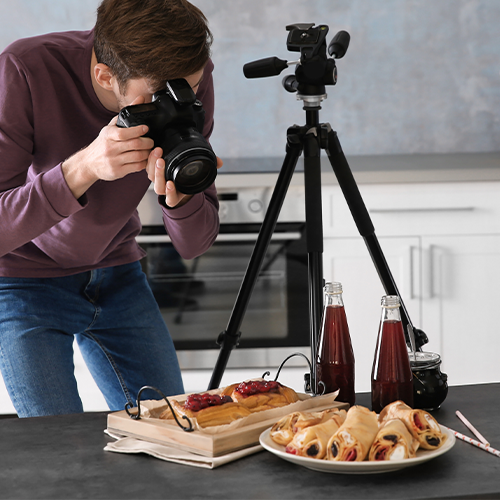Man holding camera taking photo of a plate of food