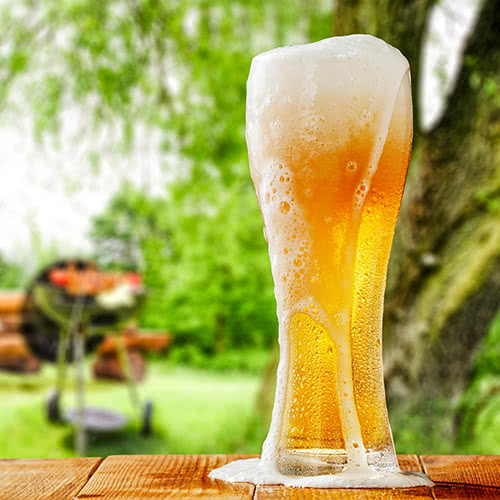 Pilsner glass overflowing with frothy beer