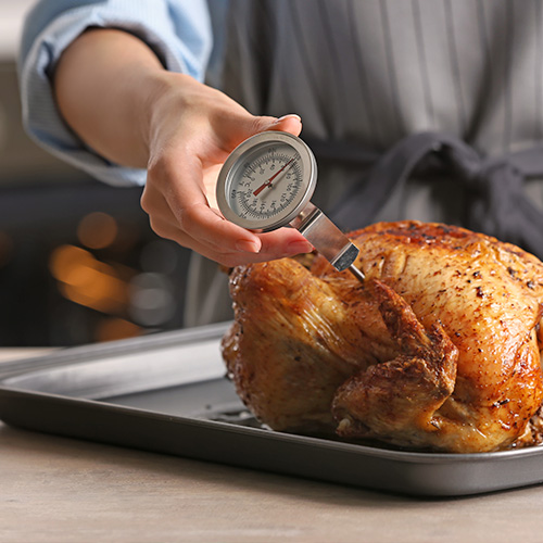 Chef holding meat thermometer in cooked turkey