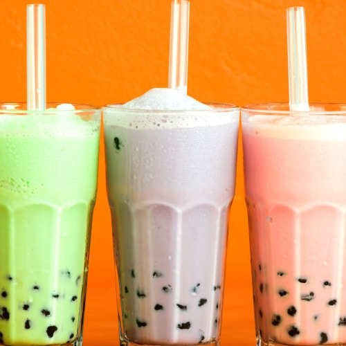 Bubble tea flavors: glasses of green tea bubble tea, taro bubble tea, and strawberry bubble tea