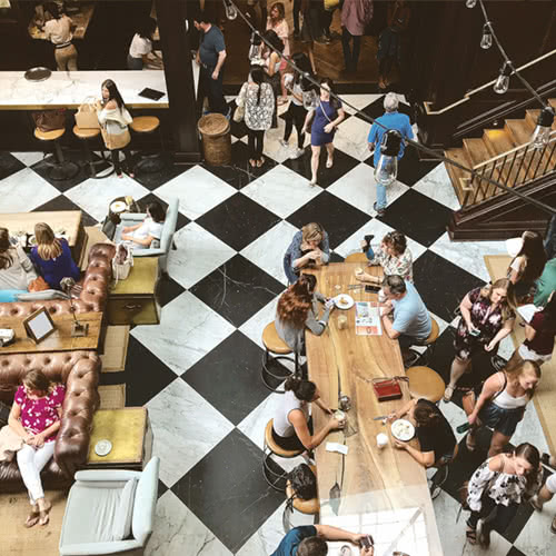 large food hall with communal seating and checkerboard flooring