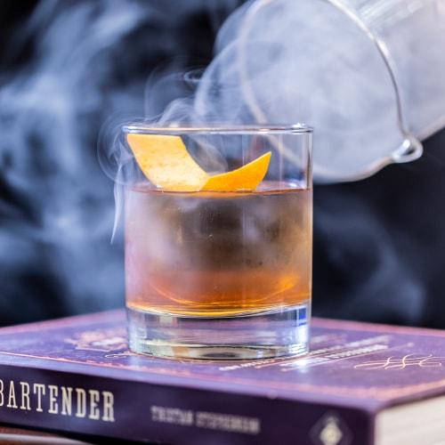 стакан дымящегося виски на обложке книги руководства бармена