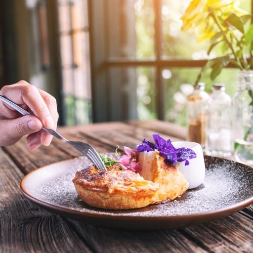 рука кладет вилку в тесто молекулярной гастрономии с фиолетовым цветком на деревянном столе