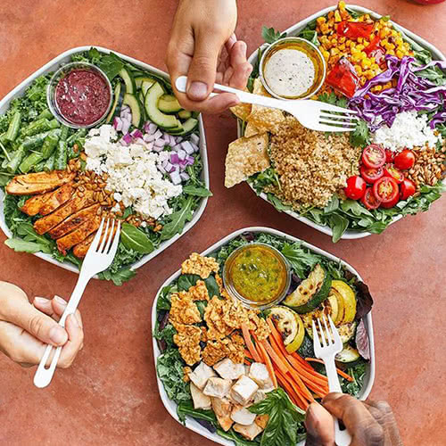 three dishes of colorful salads from Sweetgreen and hands holding forks