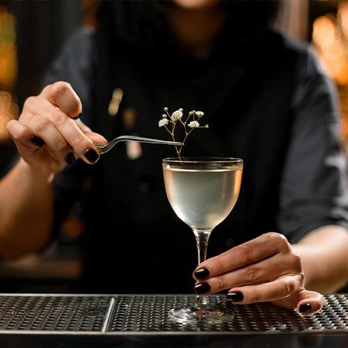 Bartender elaborando una bebida elegante con guarnición