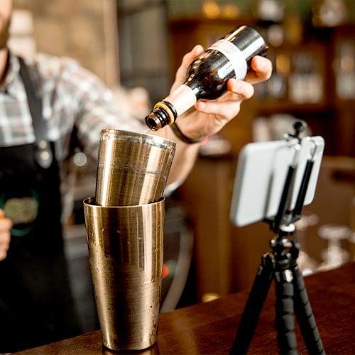 Bartender filmándose a sí mismo con un smarphone en un trípode