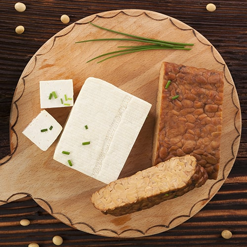 Tofu and tempeh on wooden background