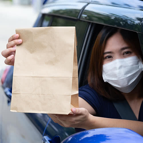 Asian woman wearing mask and holding paper bag of fast food through the window