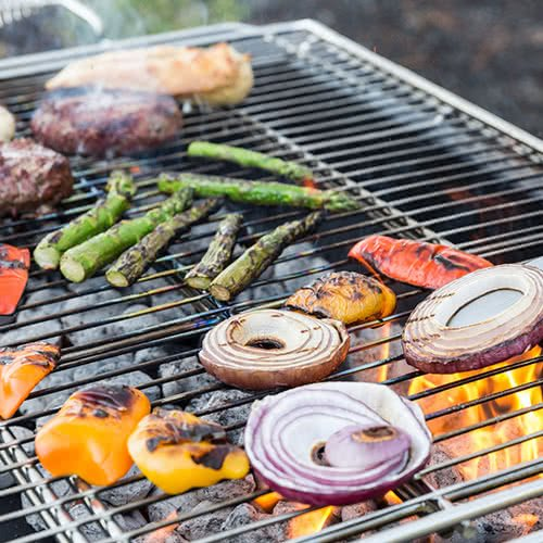 veggies and meat on a hot grill