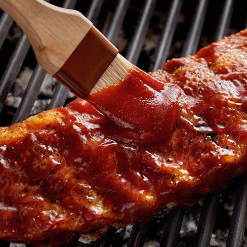 brushing sauce on meat