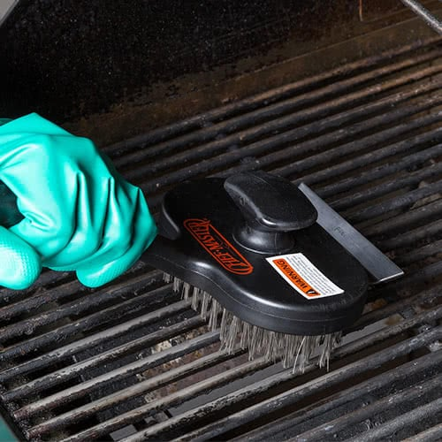 person cleaning grill grates