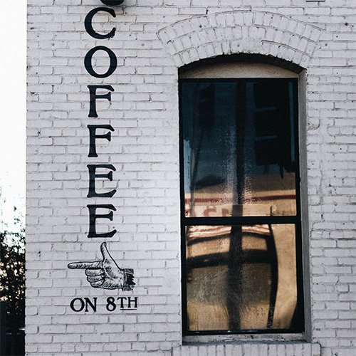 coffee on 8th painted on a brick building with window