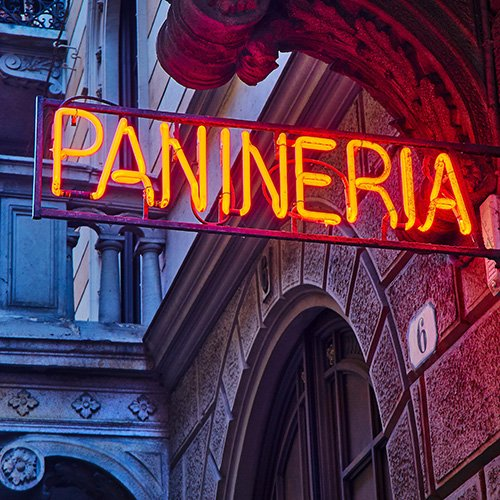 panineria neon sign board in an italian street at nightfall