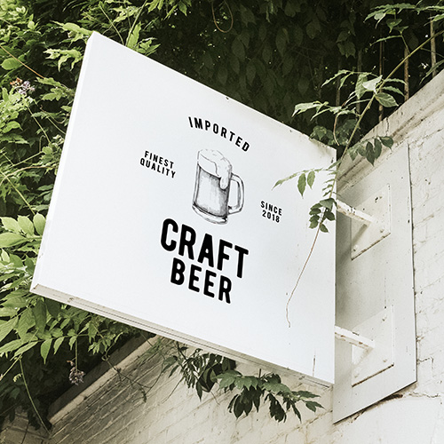 sign hanging on brick wall that says imported craft beer finest quality