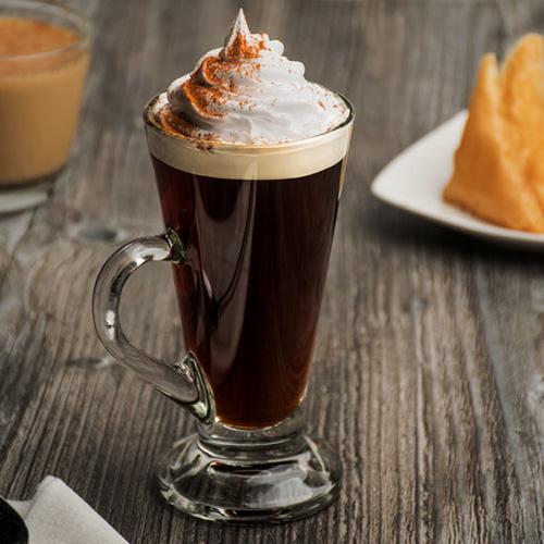 cappuccino em vidro transparente com chantilly e canela por cima