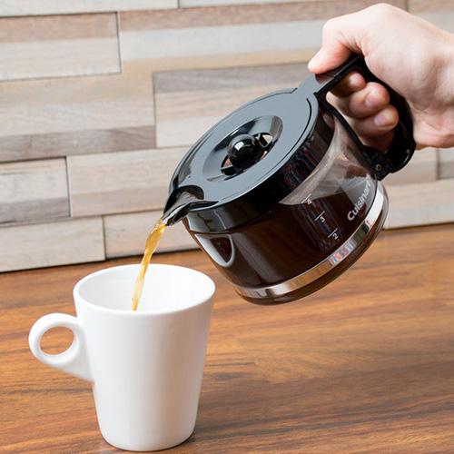 pessoa servindo café na caneca branca da cafeteira