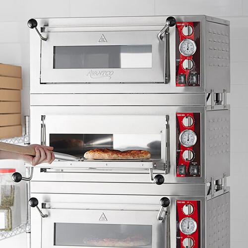 Chef removing pizza from avantco equipment triple deck pizza oven