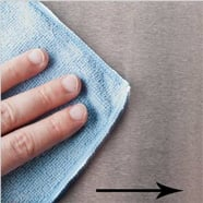 Hand cleaning a stainless steel surface with a blue microfiber towel