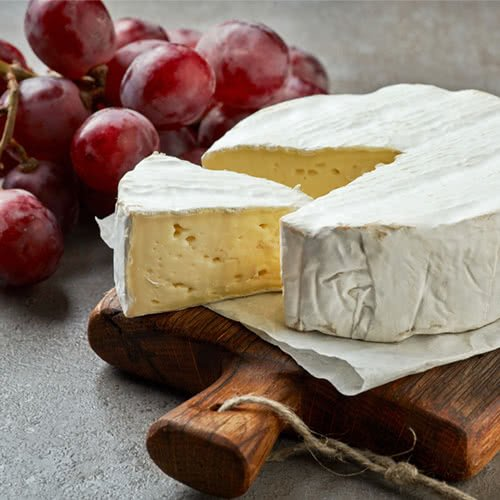 Wood serving board with a round of camembert, a wedge of camembert, and red grapes in the background