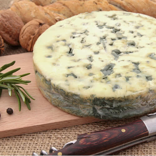 Round of fourme d'ambert on a wood serving board with a sprig of rosemary and a cheese knife
