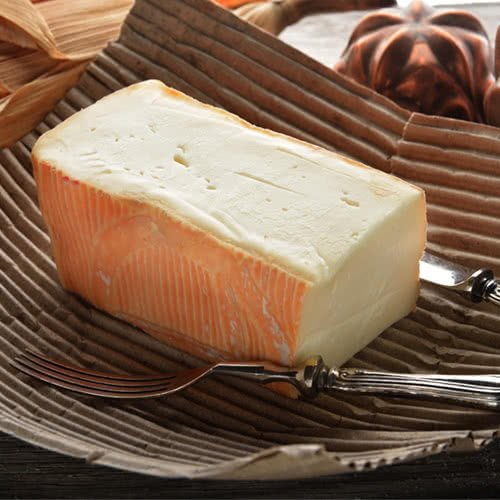 Block of taleggio on a cardboard serving tray with a fork and knife on either side of the block