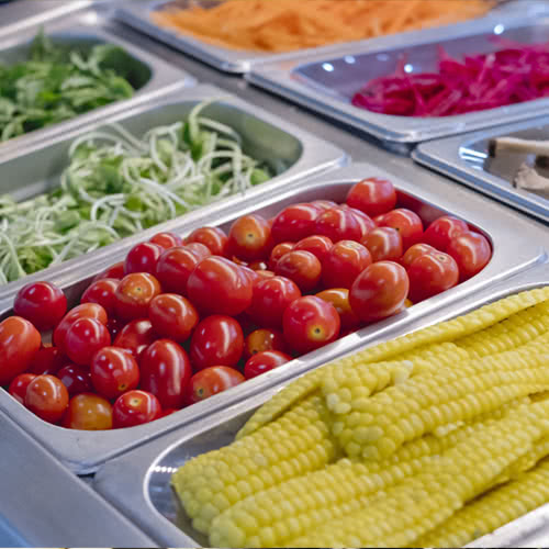 Cold food well filled with garden-fresh vegetables in a myriad of food pans